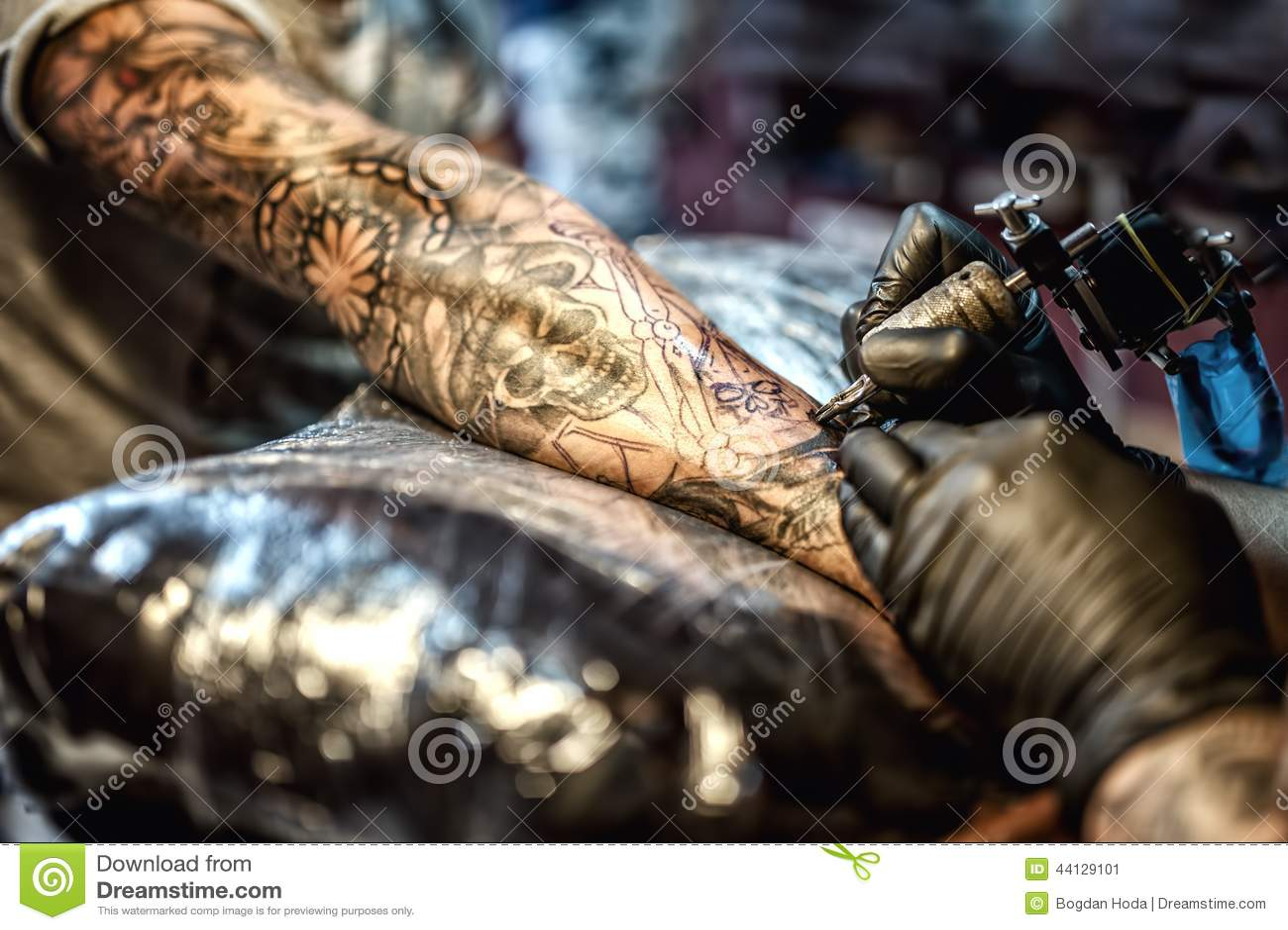 Tatúe el dibujo del artista en el brazo y en la piel del cliente