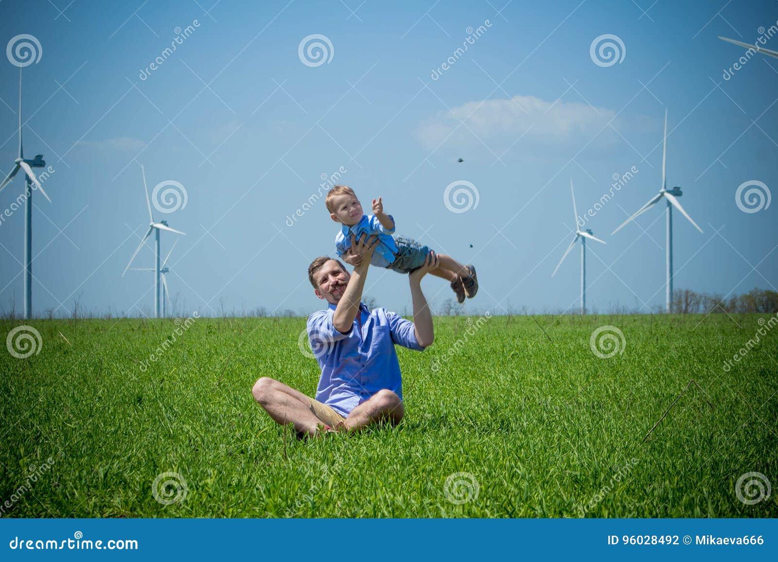 Tata podnosił jego syna i okrążający blisko silników wiatrowych