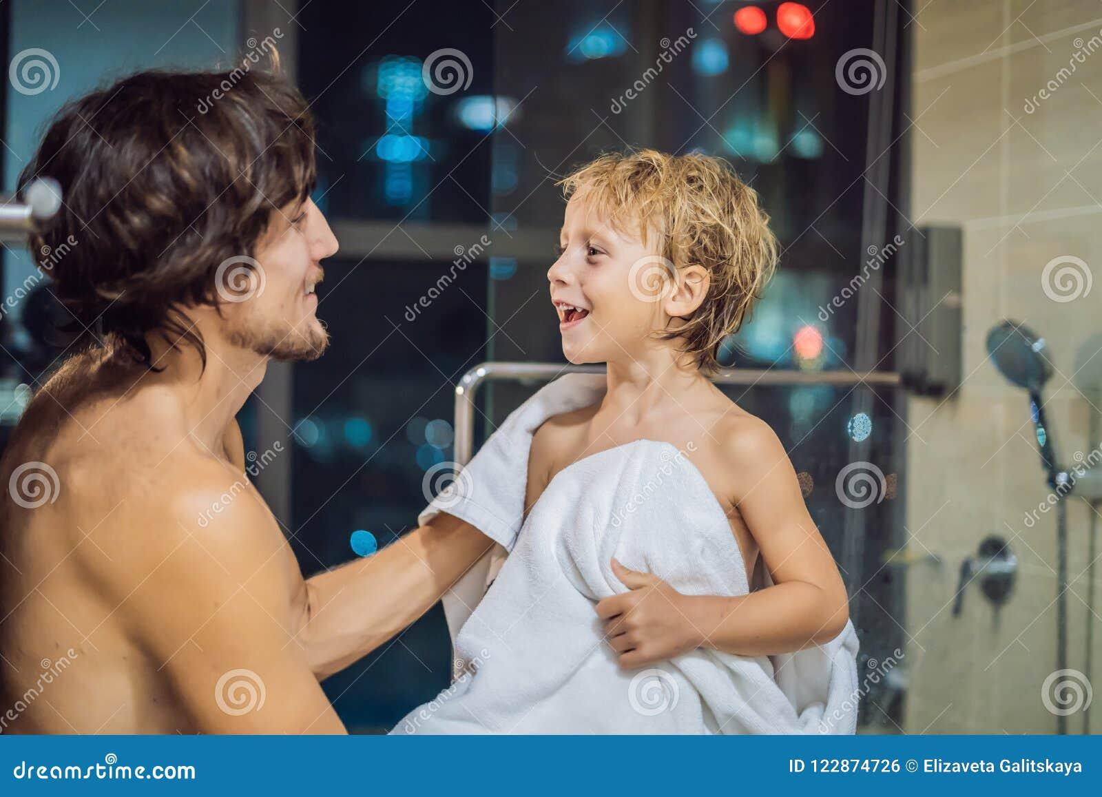Tata wyciera jego syna z ręcznikiem po prysznic w wieczór przed iść spać na tle okno z panoramicznym