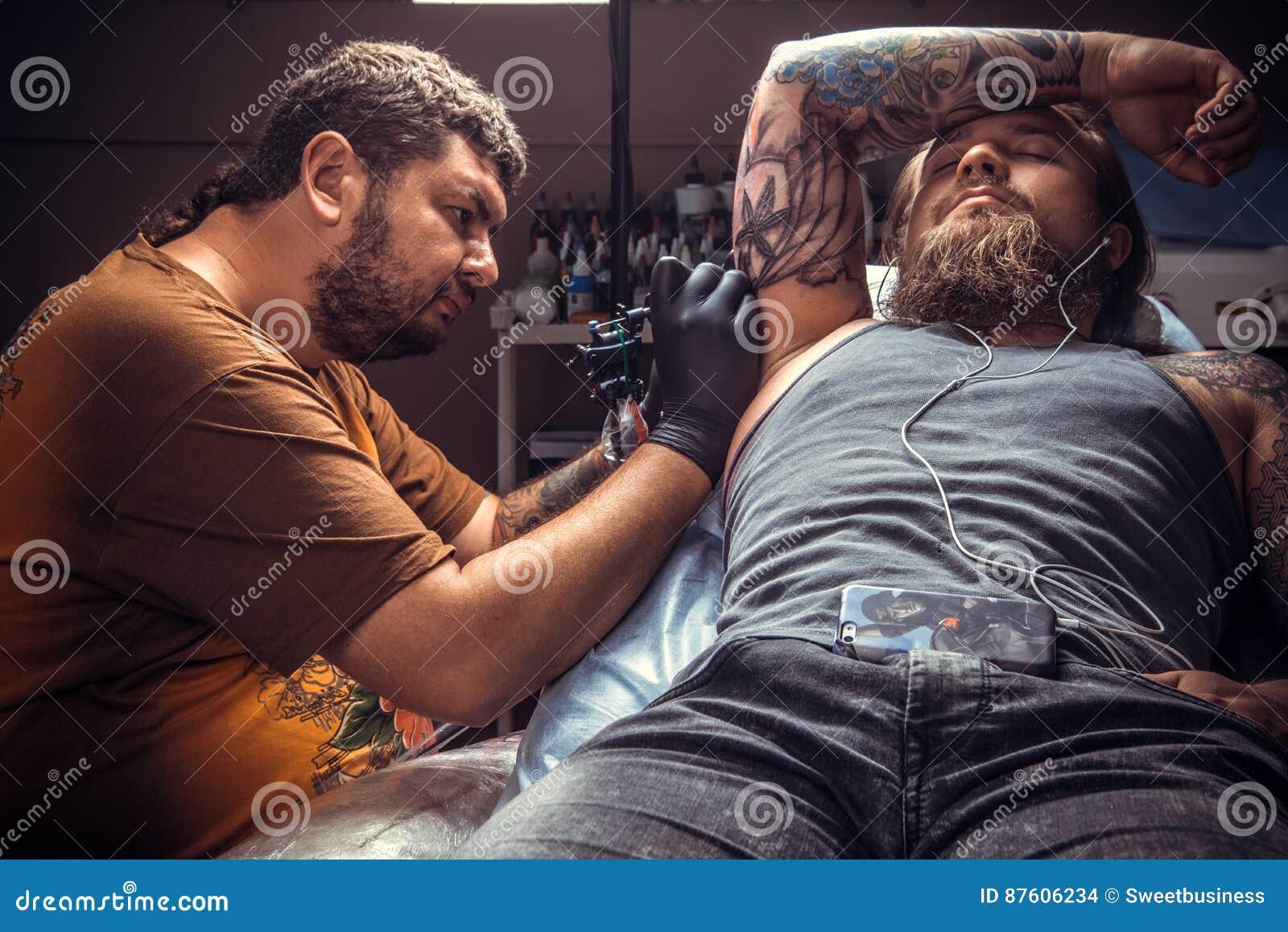 00d646f01 Tattoo specialist makes cool tattoo in tattoo parlour/Professional tattooer  showing process of making a tattoo in salon.