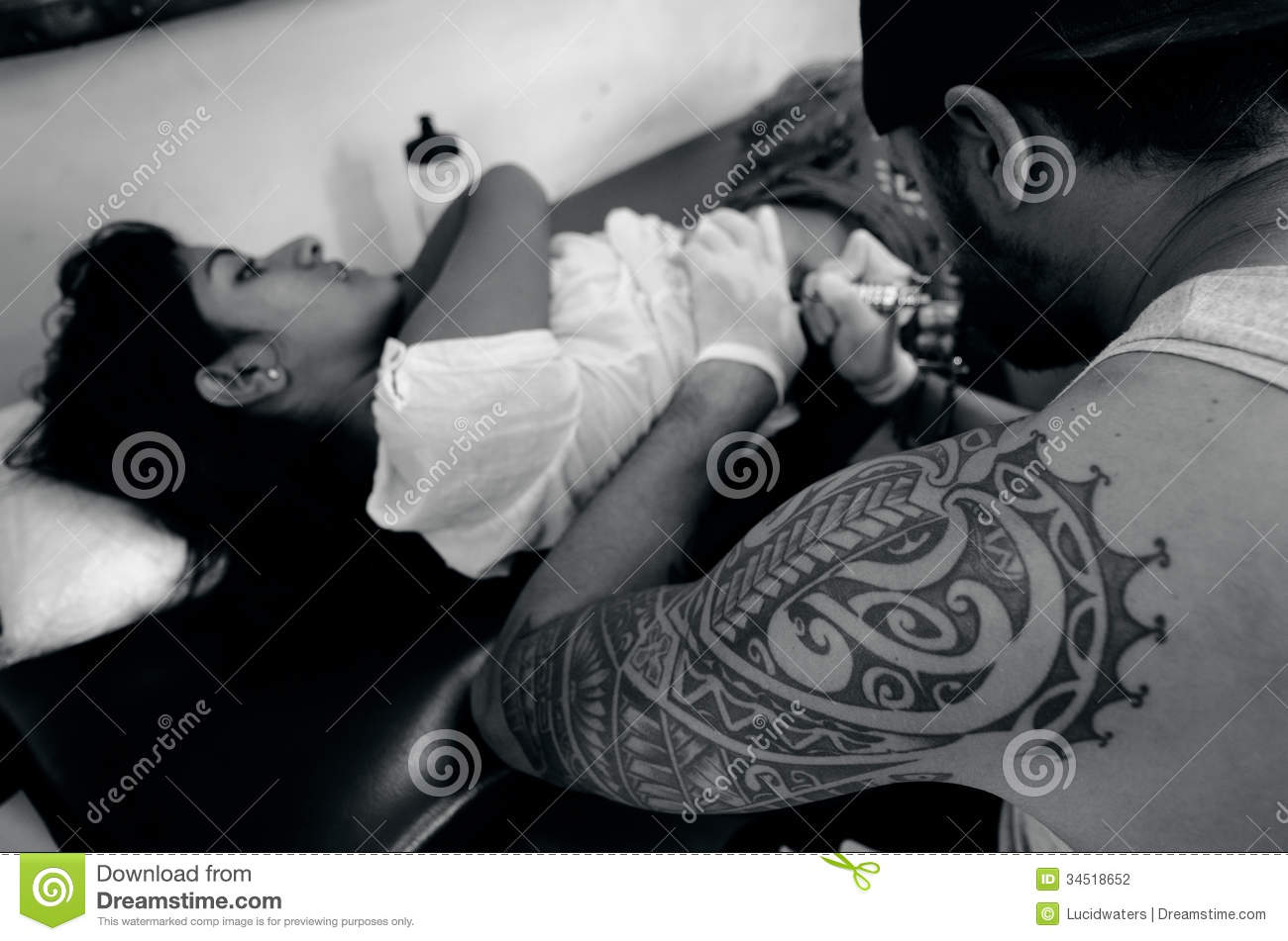 Pacific Island male tattoo artist draws a design on back of young ...