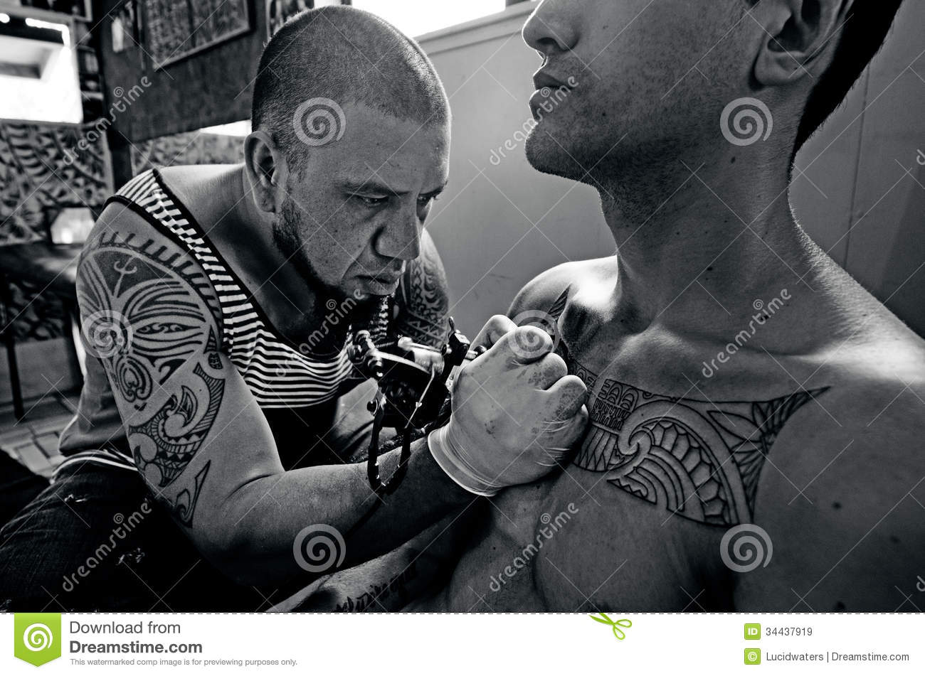 Pacific Island male tattoo artist draws a design on a chest of a young