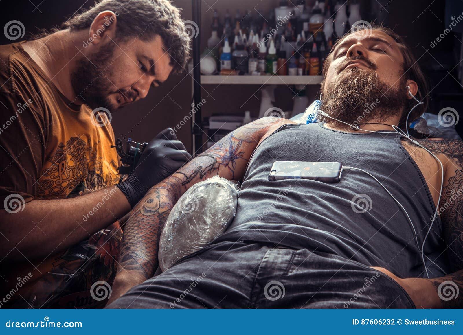c160f11b2 Tattooer working tattooing in tattoo studio./Professional tattoo artist  doing tattoo in tattoo parlour. More similar stock images
