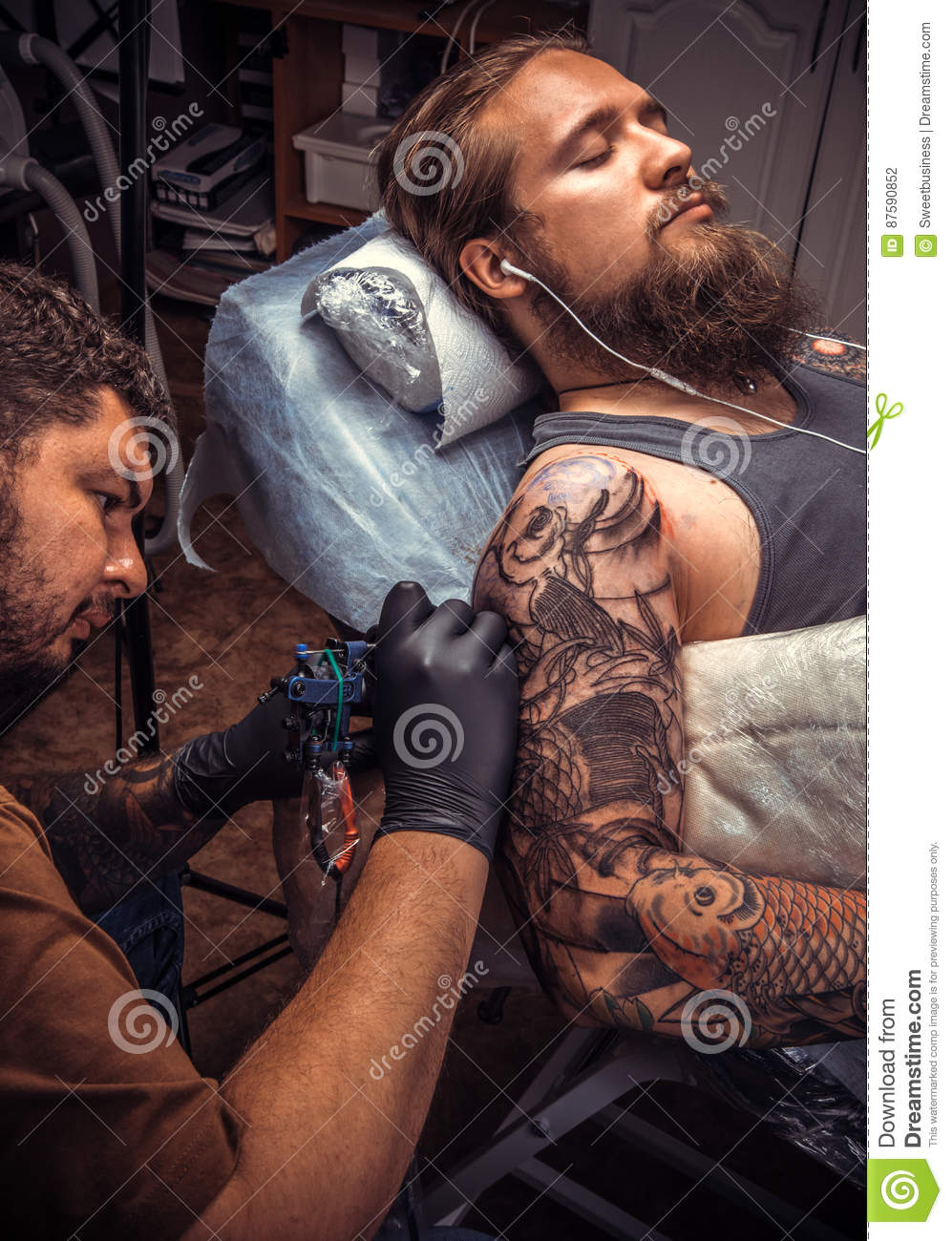 Tattoo master doing tattoo in tattoo parlor royalty free for Working man tattoo