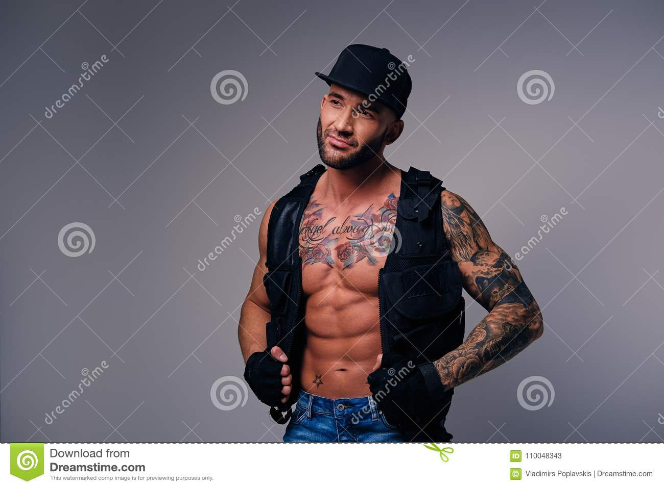 Tattooed Male Dressed In A Jeans, Cap And Waistcoat On A Naked T Stock Image - Image -3167