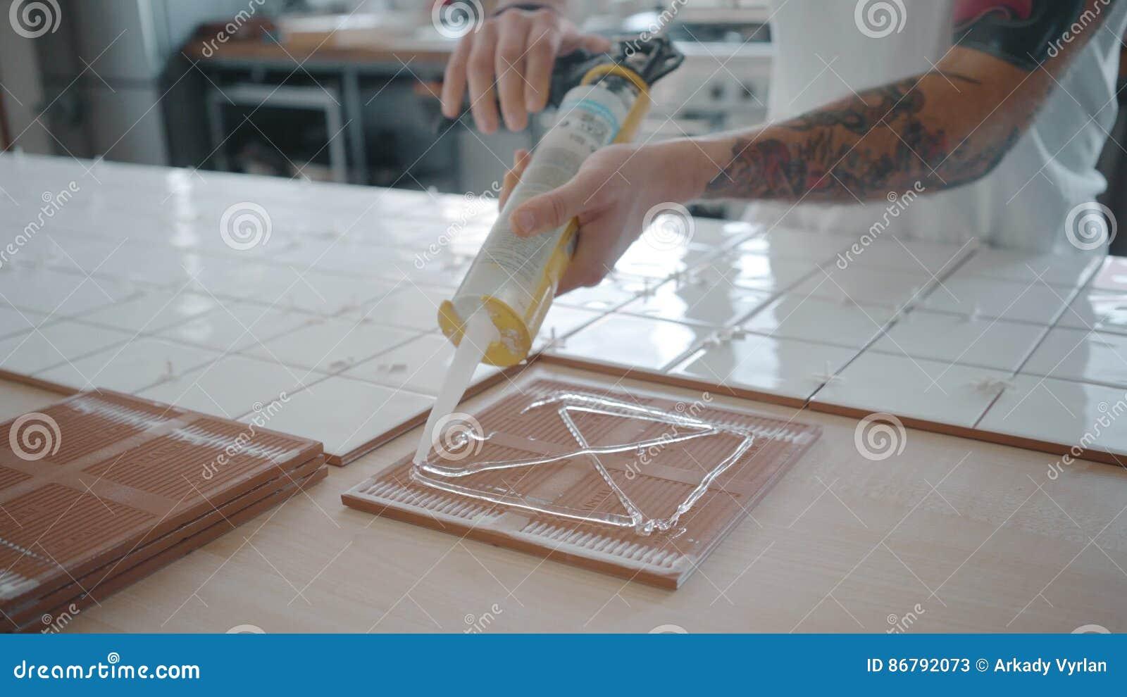 Tattooed Man Applies Ceramic Tiles On Kitchen Table Set Stock Video