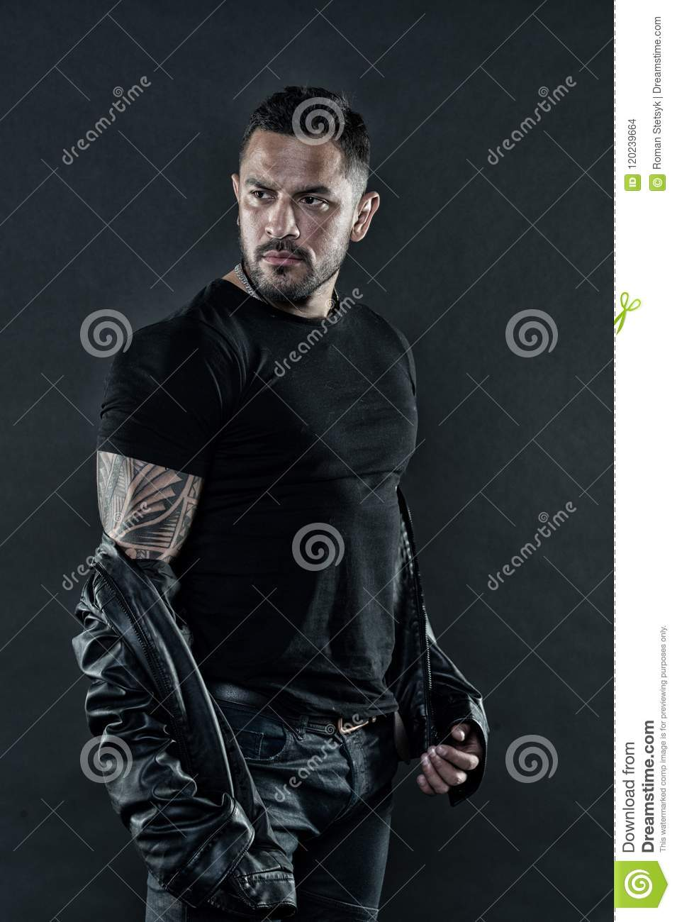 dc8b848c4 Tattooed man in tshirt and leather jacket. Bearded man show tattoo on  strong arm.