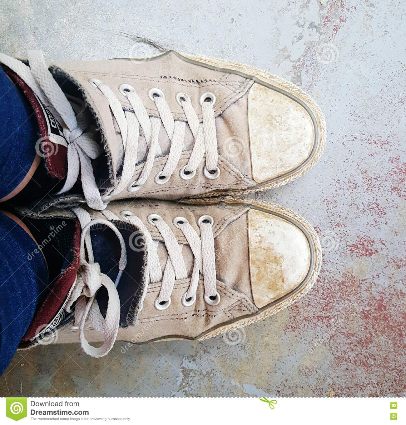 Dirty converse style lace up sneakers in grey on messy floor. Ripped and  broken fc290c5d3