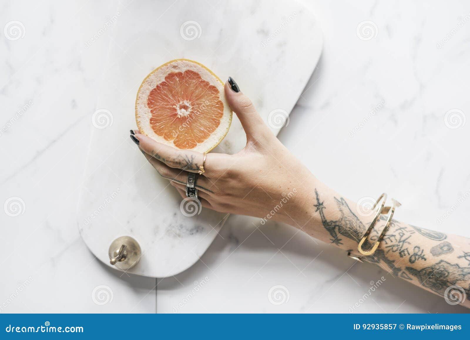 Tatuaż kobiety ręka Dostaje pomarańcze z Marmurowym tłem