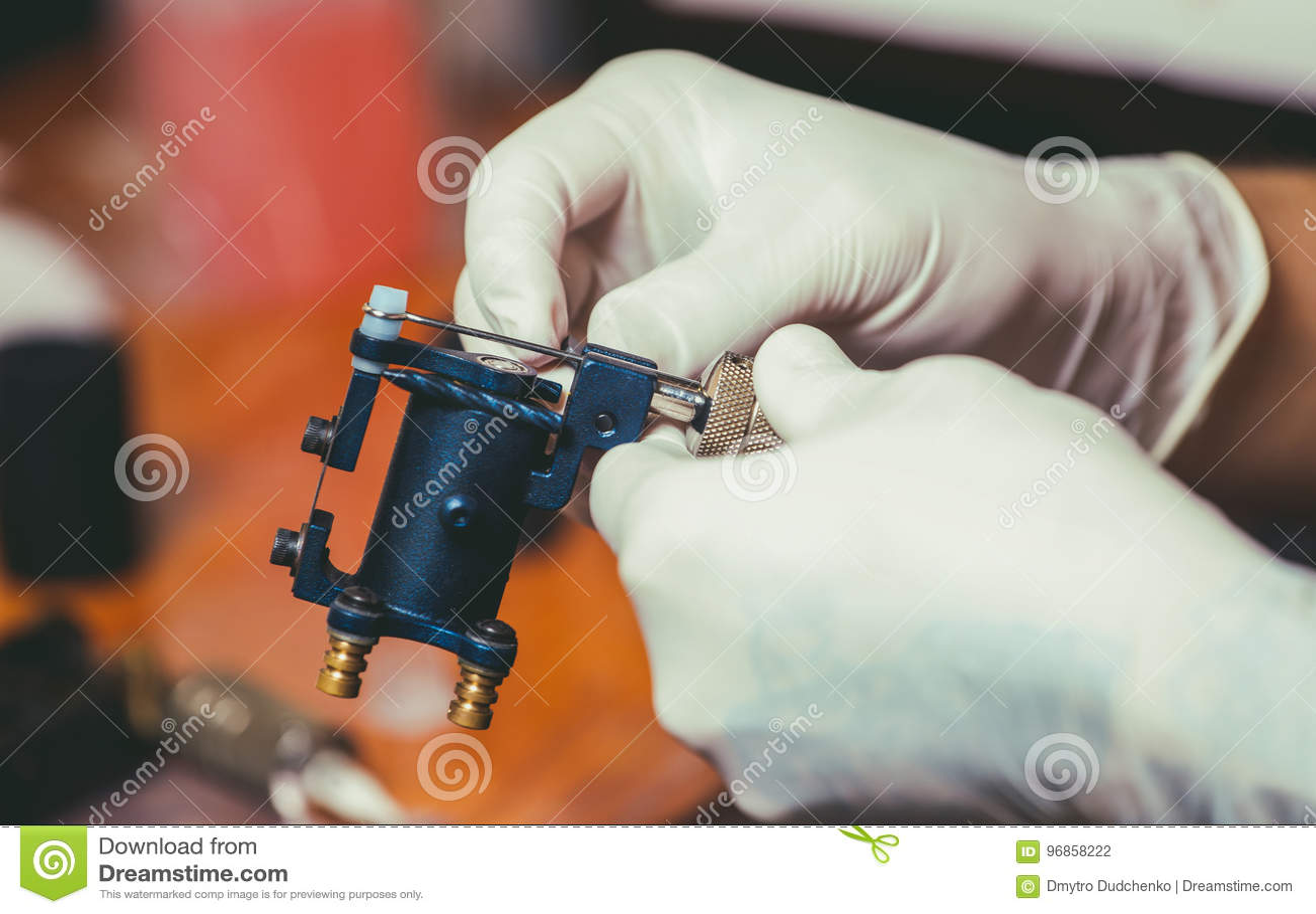 Tatuażu artysta w gumowych białych rękawiczkach dostaje przygotowywający robić tatuażowi w salonie
