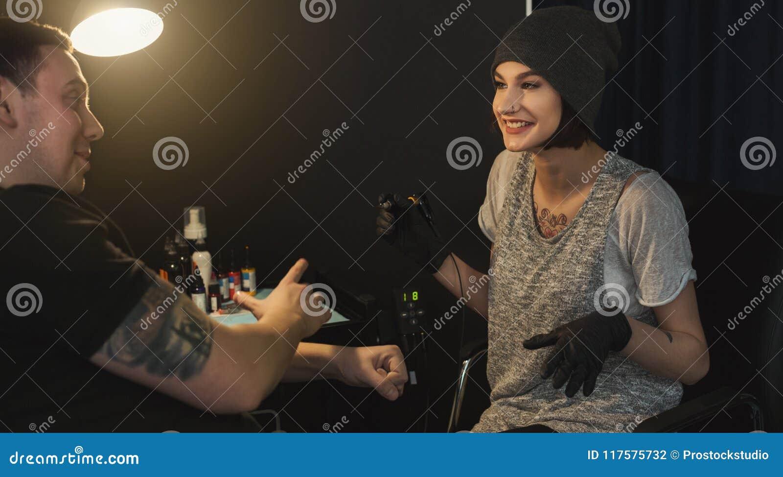 Tatuatore allegro delle donne che fa tatuaggio con la macchina del  tatuaggio sul braccio maschio Professione femminile insolita caf7d9cd9623