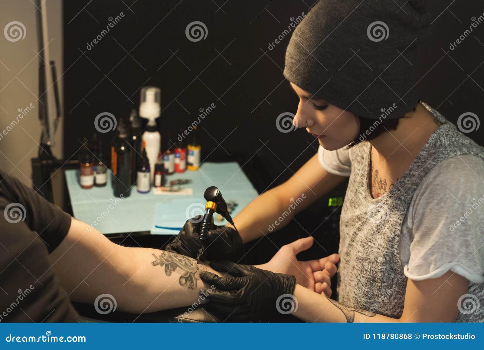 Tatuatore concentrato della donna che fa tatuaggio con la macchina del  tatuaggio sul braccio maschio Professione femminile insolita e5cfb739cff2
