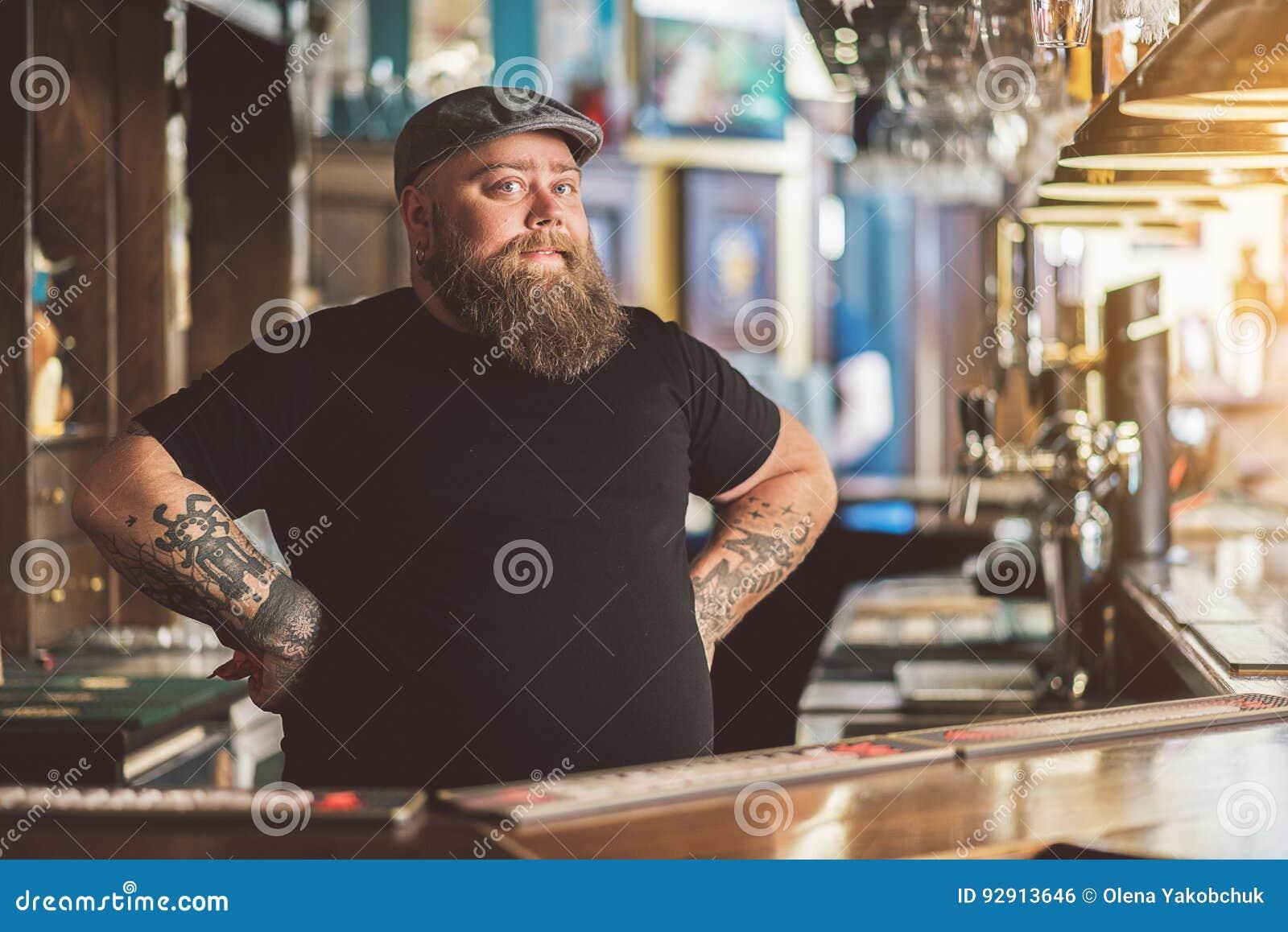 Tatuujący barman pracuje w pubie