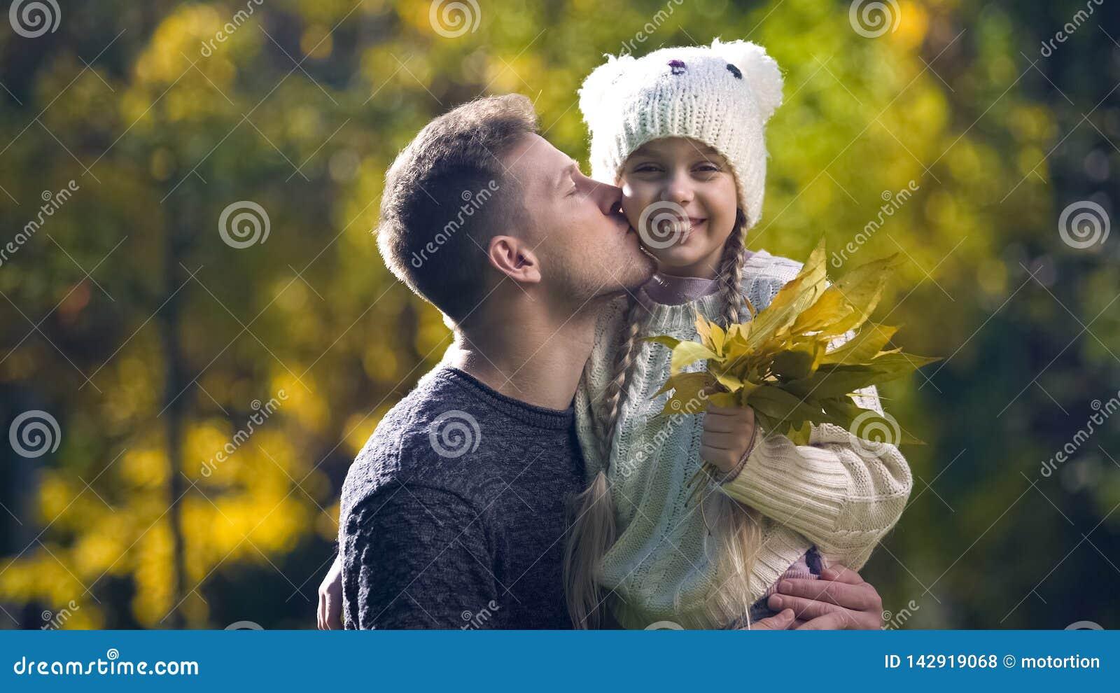 Taty mienia córka w śmiesznym kapeluszu i całowaniu, czas wolny wpólnie, jesieni przespacerowanie