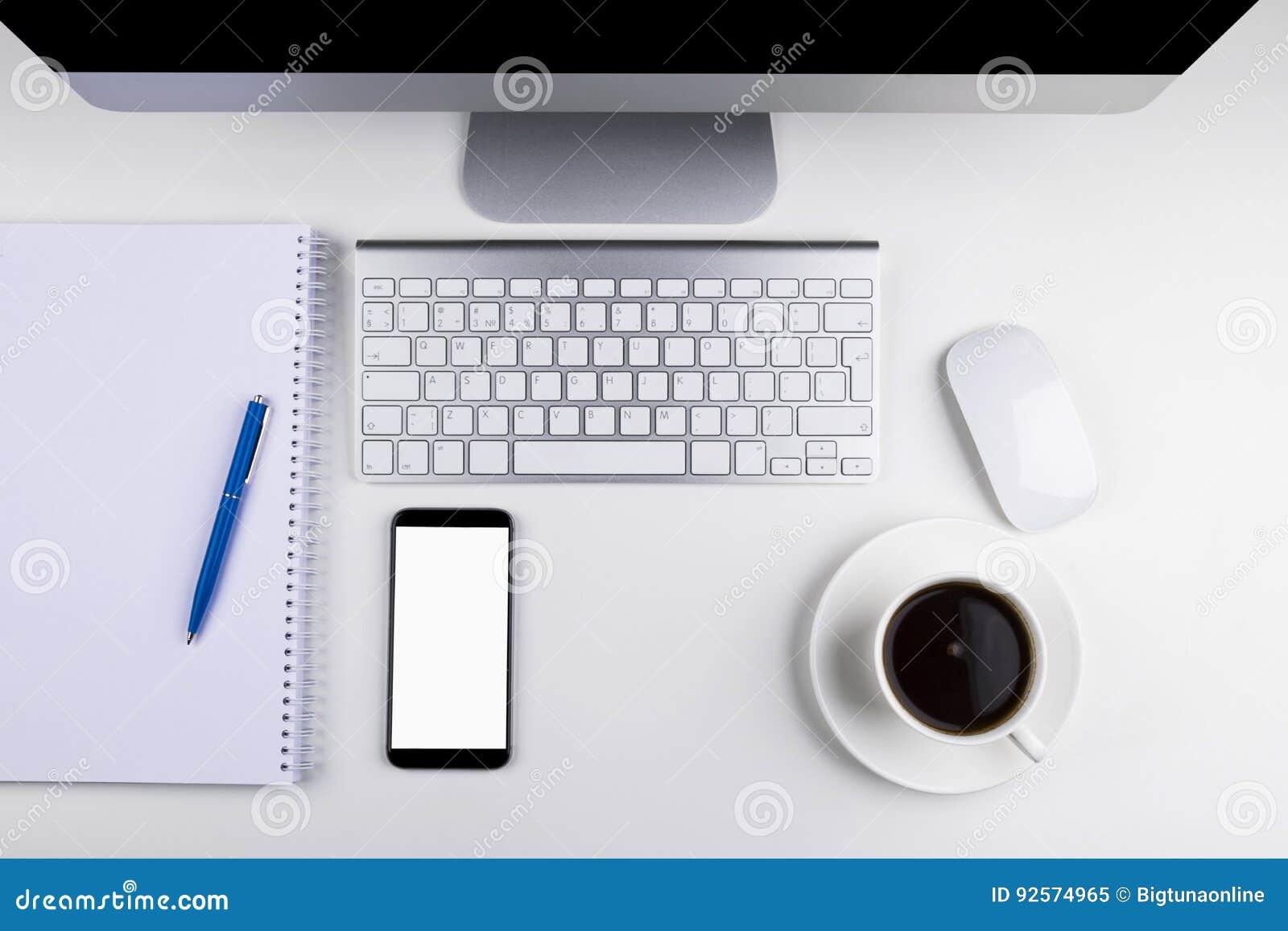 Tavola dell ufficio con il computer, la tastiera di computer senza fili ed il topo, tazza di caffè, smartphone della compressa co