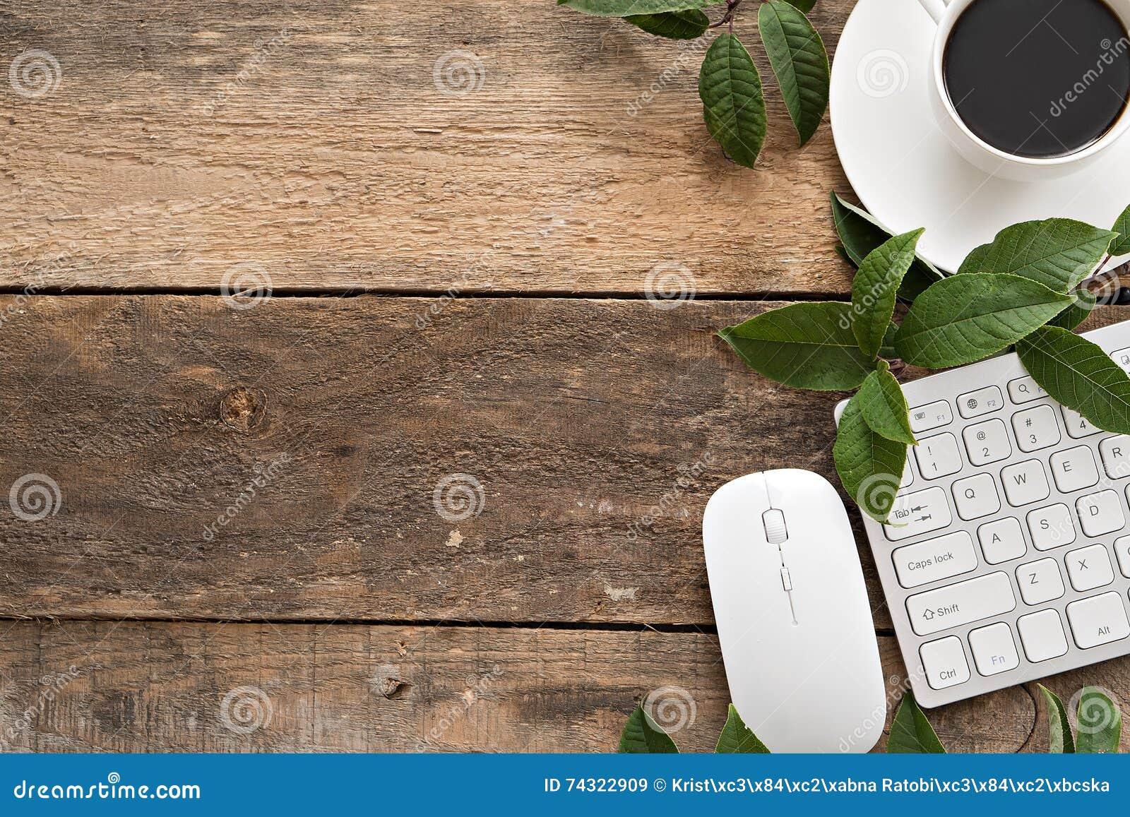 Tavola della scrivania con il computer, i rifornimenti e la tazza di caffè