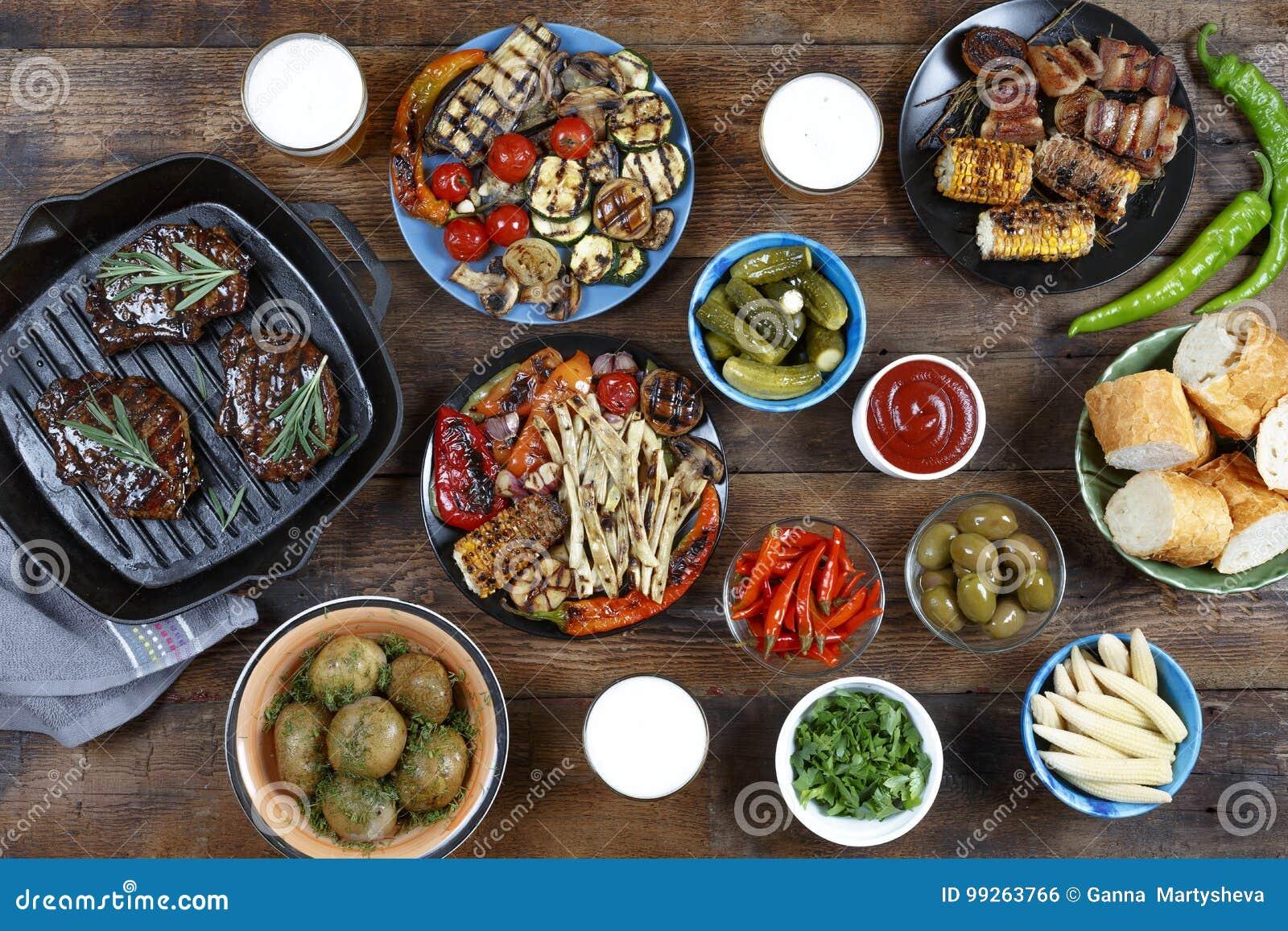 Tavola di cena con la griglia della carne, le verdure del bbq, le insalate, le salse, gli spuntini e la birra, vista superiore