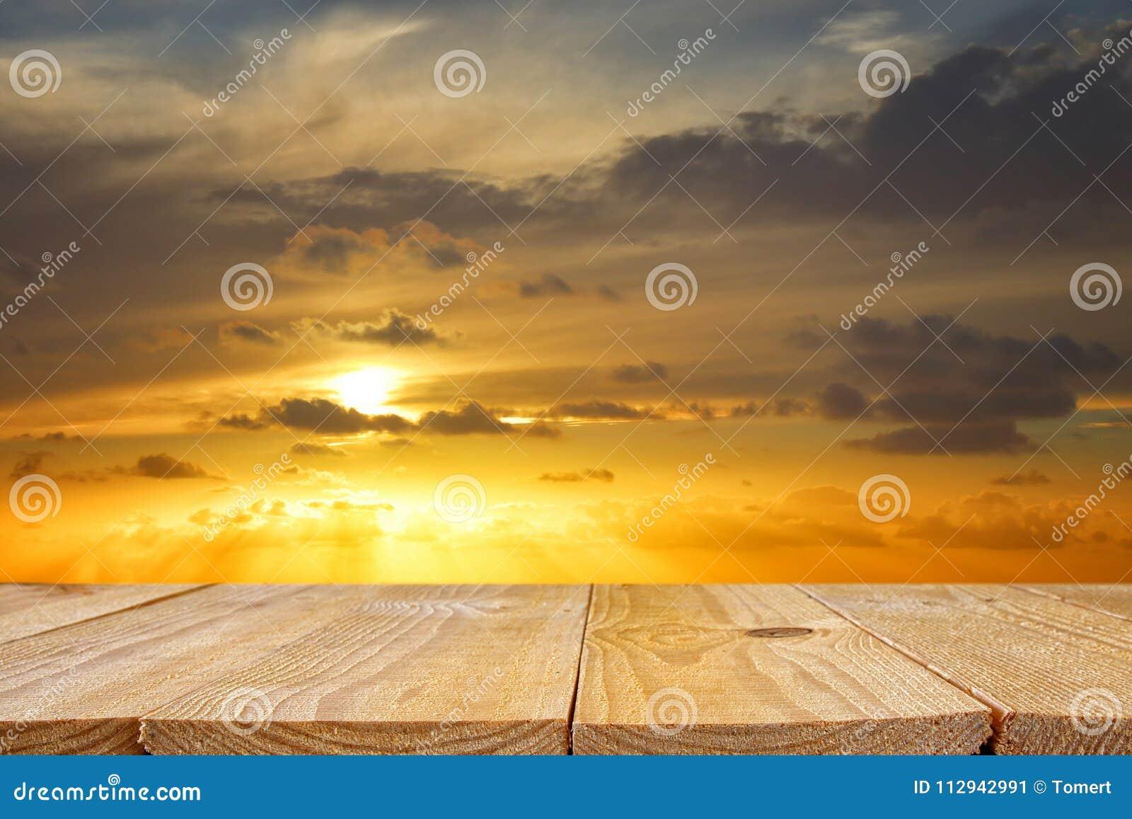 Tavola di legno del bordo davanti al tramonto dorato fondo di esposizione del prodotto