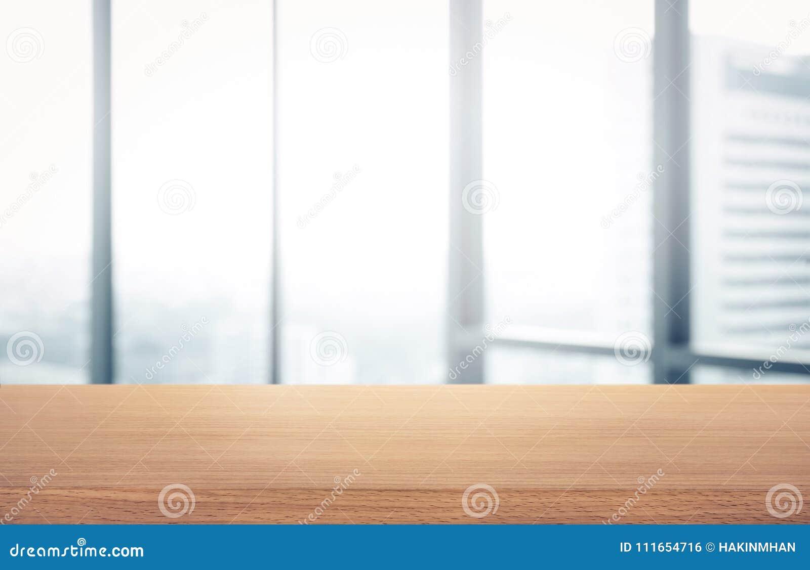 Tavola di legno vuota con la vista dell ufficio della stanza della sfuocatura e della città della finestra