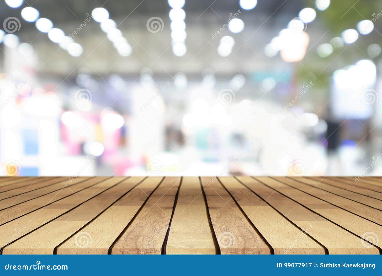 Tavola di legno vuota di prospettiva sopra il backgr vago del centro commerciale
