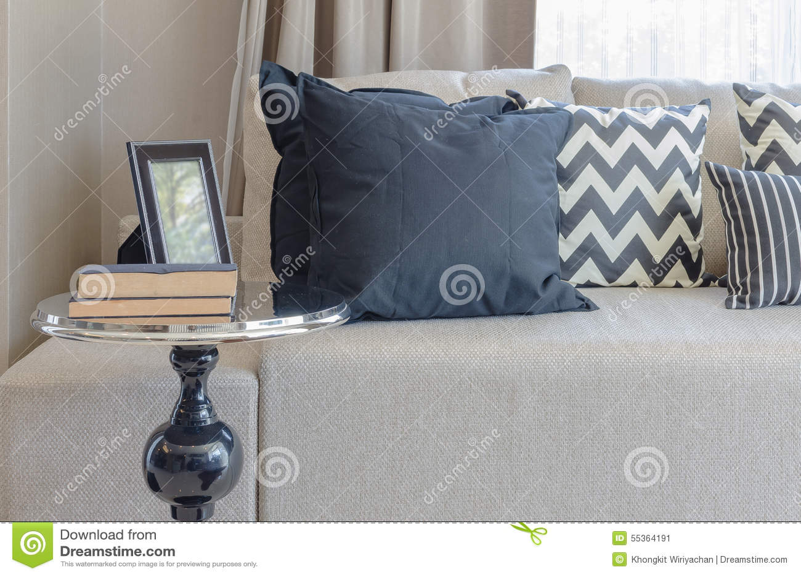 Tavola rotonda nera nello stile classico con i cuscini ed il sofà