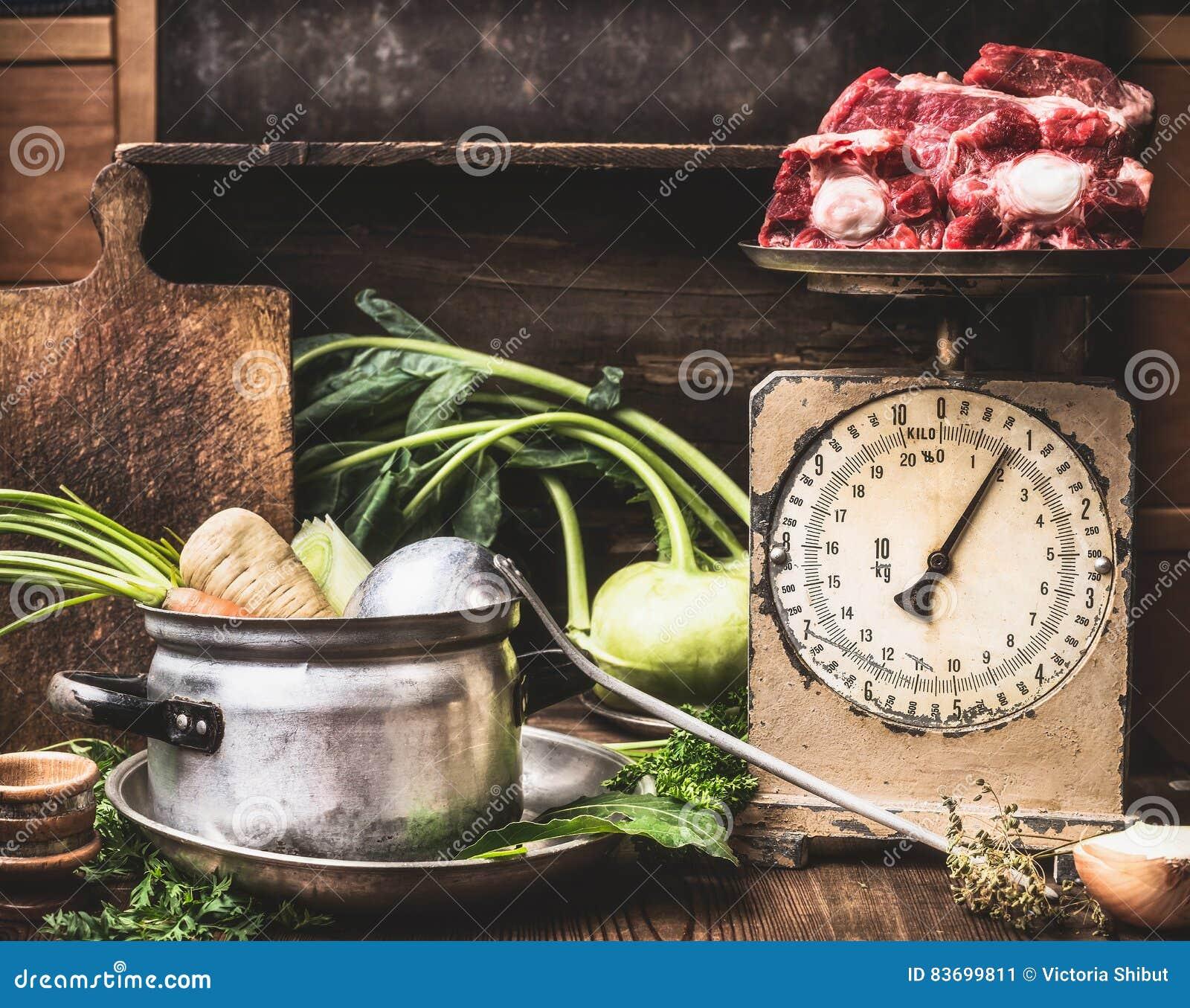 Tavolo da cucina con la cottura del vaso, siviera, verdure e vecchio pesatore con carne cruda, preparazione di minestra, brodo o