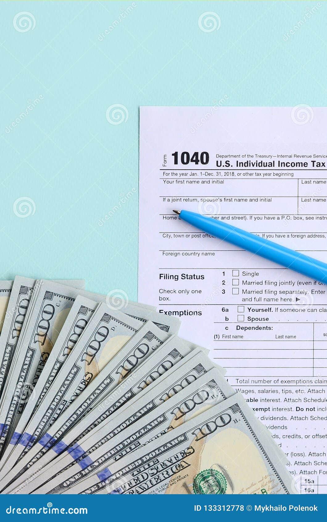 1040 Tax Form Lies Near Hundred Dollar Bills And Blue Pen On