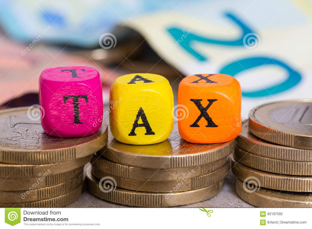TAX letter cubes on coins concept