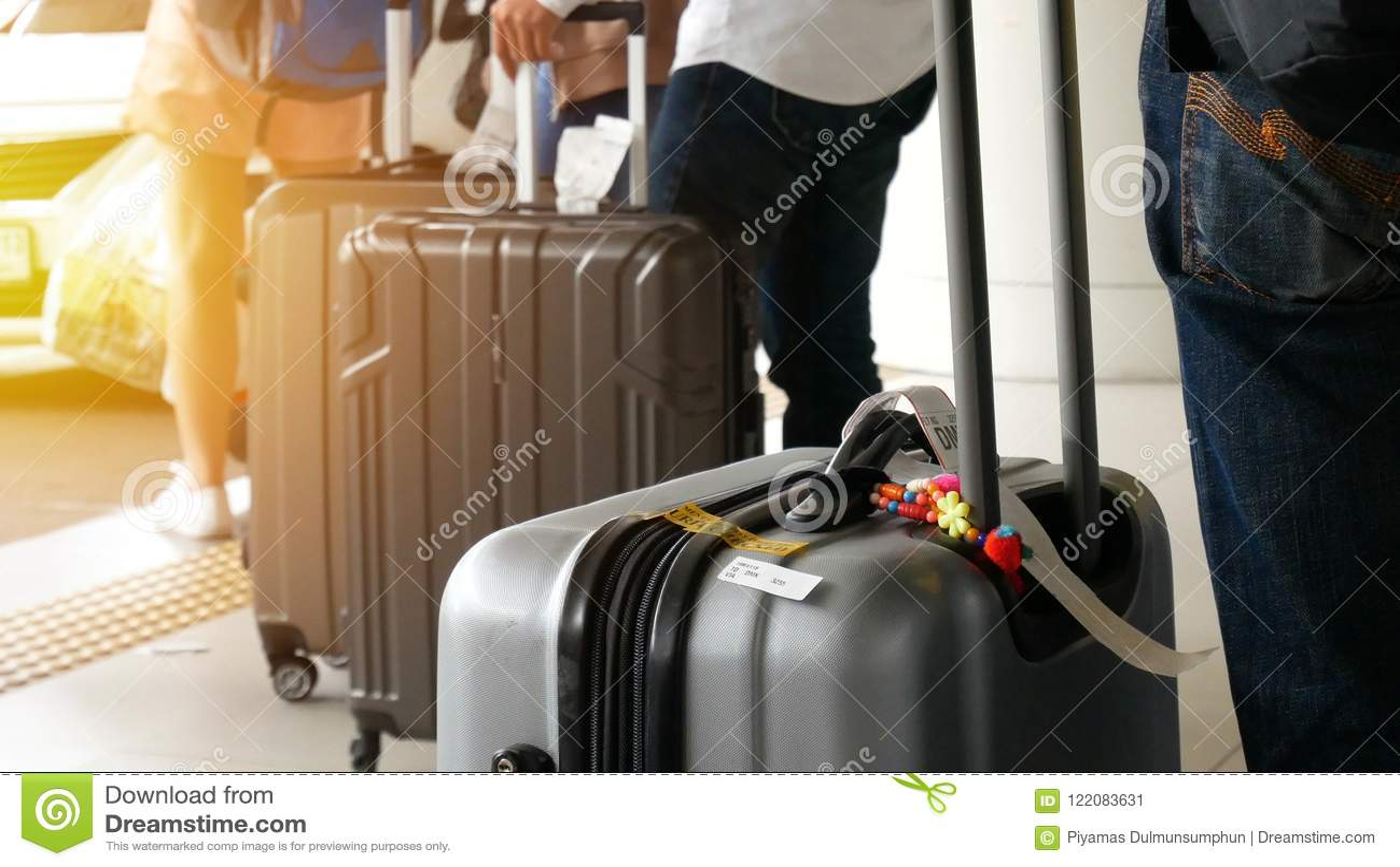 Taxi del aeropuerto pasajero con el equipaje grande del rodillo que se coloca en la línea para cola del taxi que espera en el est