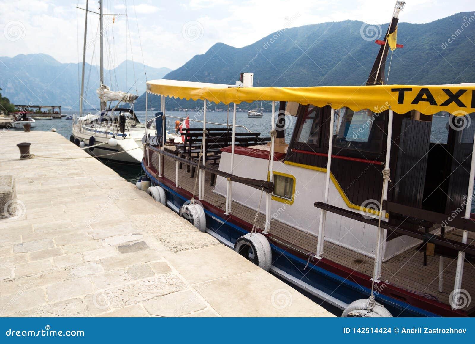 Taxi del barco en el embarcadero Embarcadero de piedra