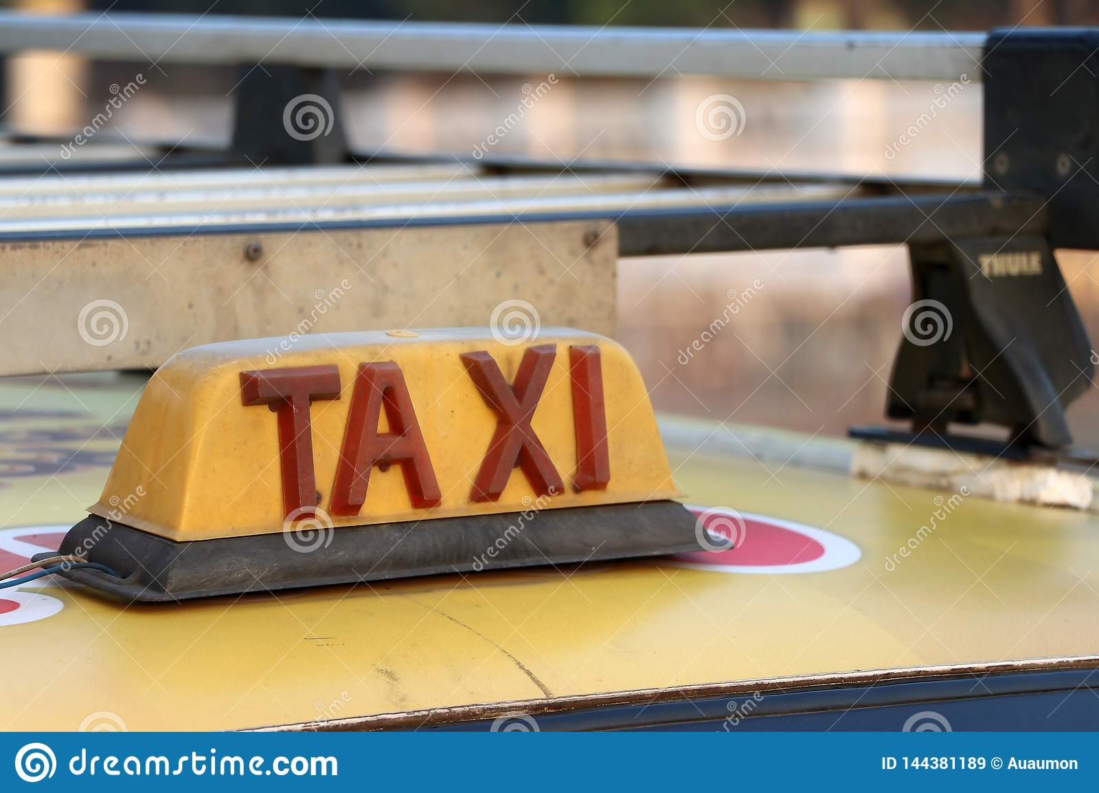 Taxi light sign or cab sign in drab yellow color with red text on the car roof