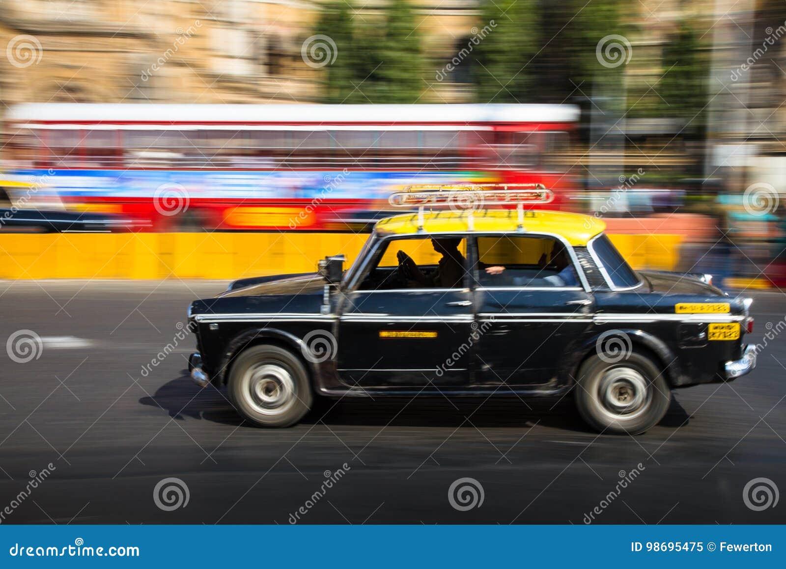 Taxi negro y amarillo tradicional viejo en el movimiento representado con la toma panorámica de la falta de definición de movimie