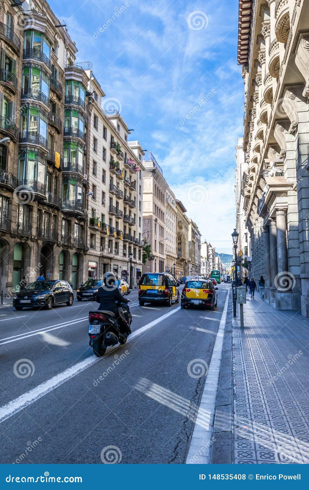 Taxicabines, privé auto s en een motorrijder op een zonnige dag in de straten van Barcelona en voetgangers die op de weg lopen
