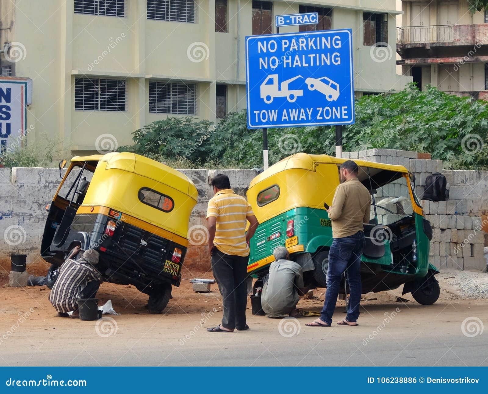 Taxichaufförer på gatan av Bangalore som reparerar denrickshaw bilen, tuk-tuk