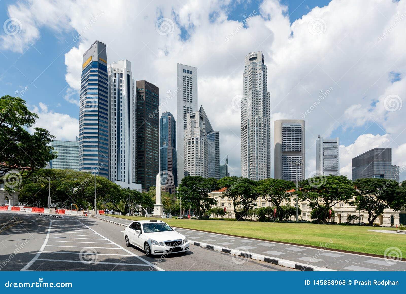 Taxitaxi som kör i väg i det Singapore centret med Singapore skyskrapor som bygger i bakgrund askfat