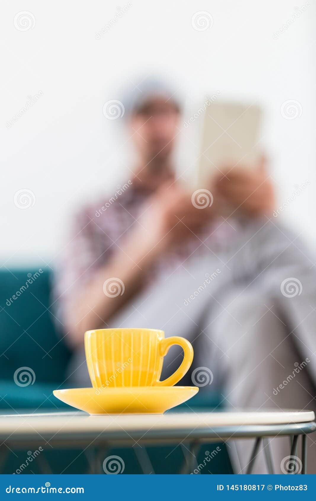 Taza amarilla de café en la pequeña tabla y de hombre de negocios de moda con la tableta digital en el fondo