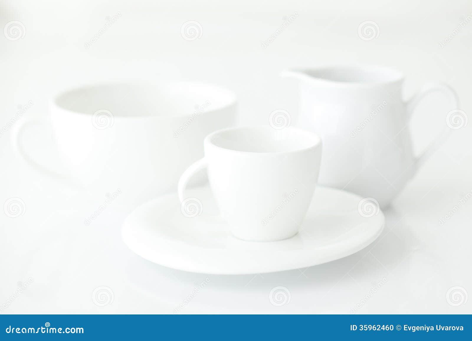 Taza con el jarro del platillo y de leche