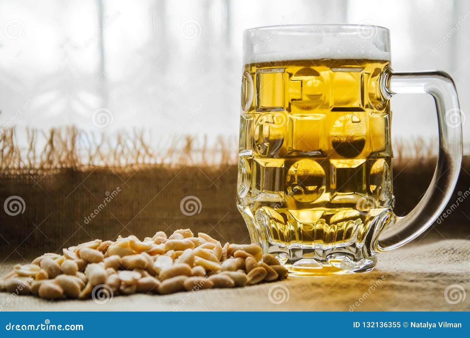 Taza con la cerveza y los cacahuetes salados en la tabla