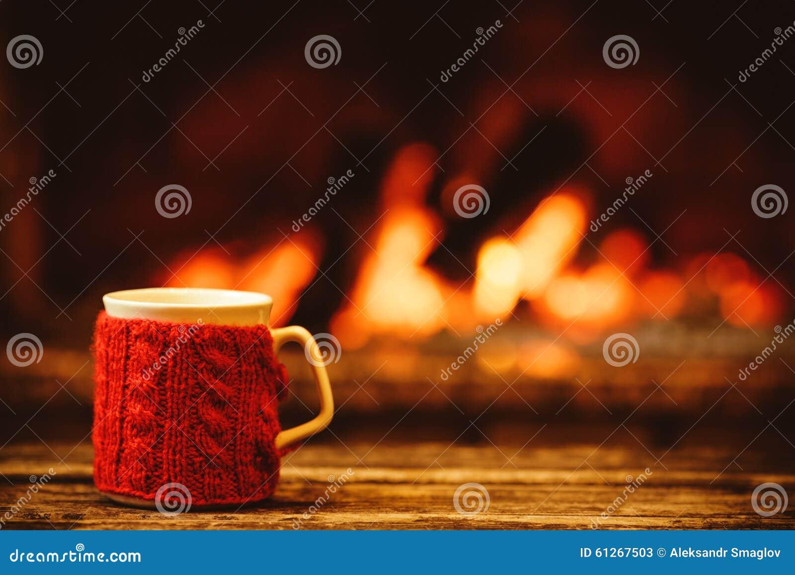 Taza de bebida caliente delante de la chimenea caliente La Navidad c del día de fiesta