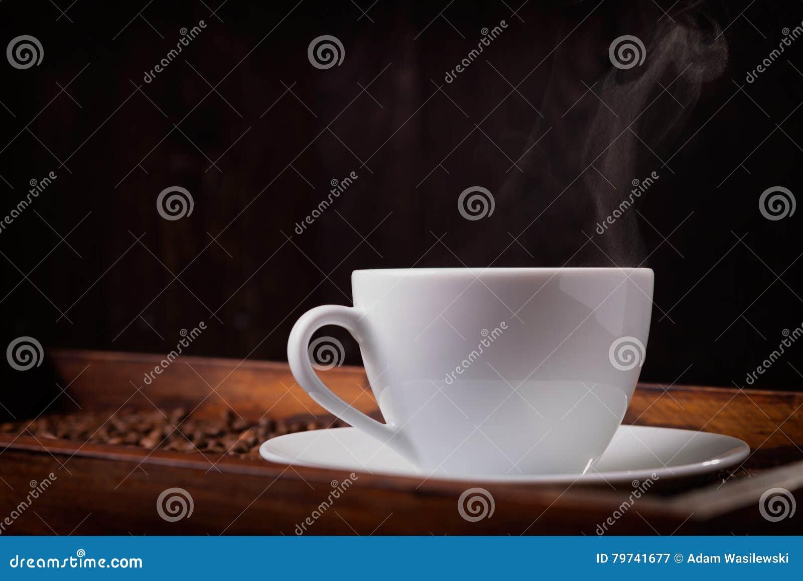 Taza de café caliente en fondo oscuro