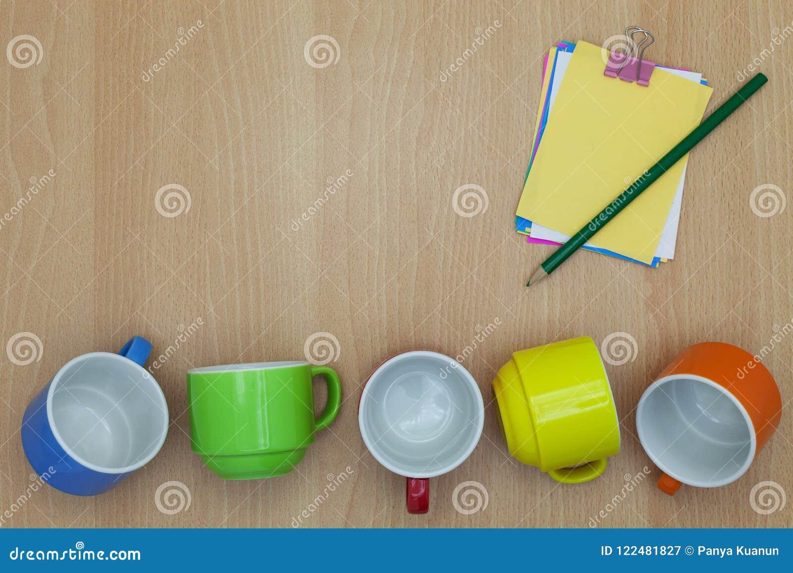 Taza de café colorida con la nota de papel, lápiz en el fondo de madera