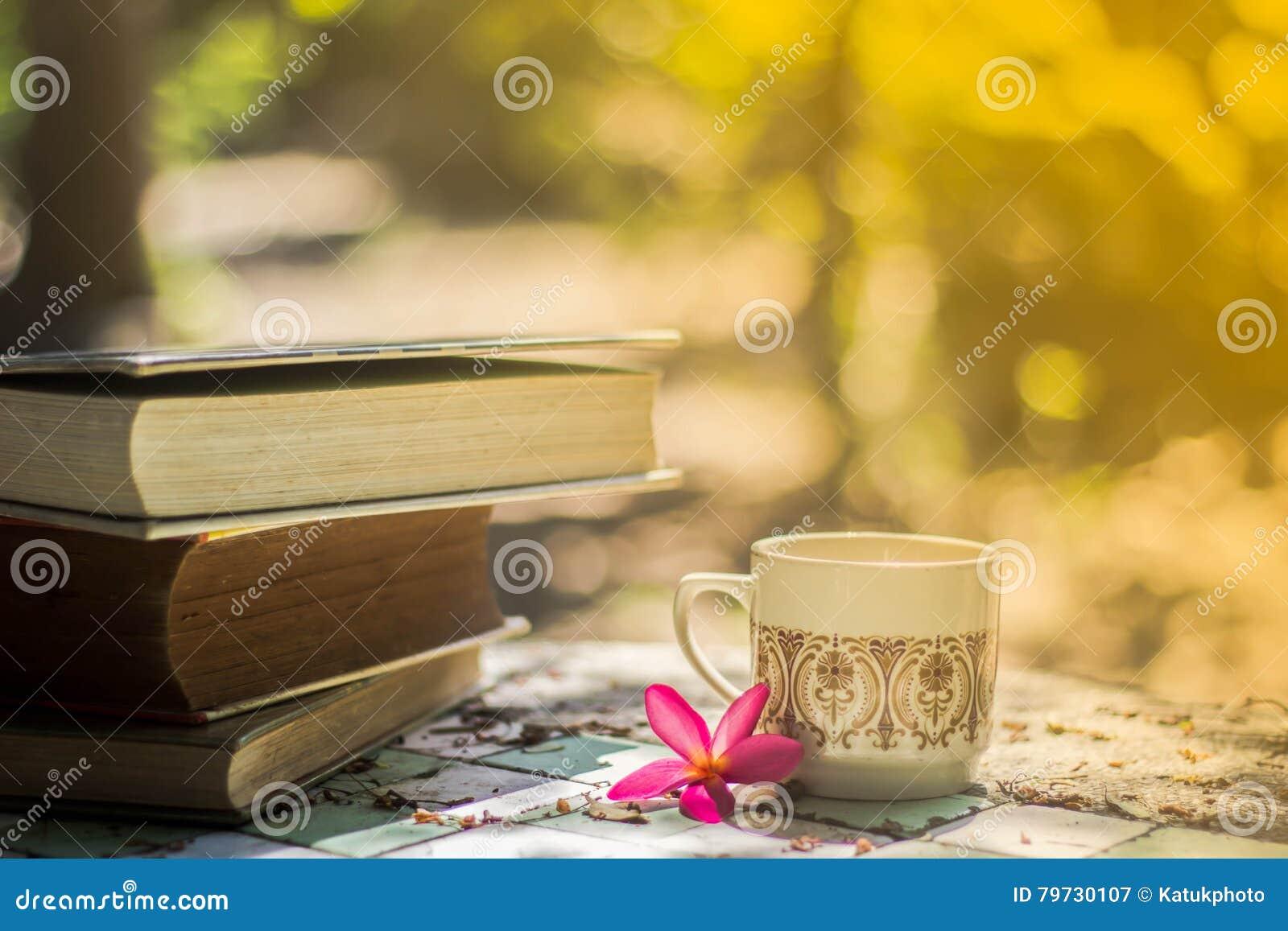 Taza de café con el escritorio de la flor, libro suave de la falta de definición del fondo del foco