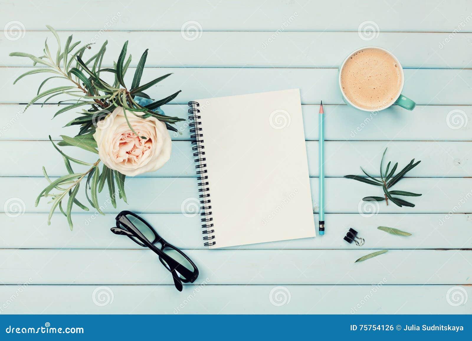Taza de café de la mañana, cuaderno limpio, lápiz, lentes y flor color de rosa del vintage en florero en la opinión de sobremesa