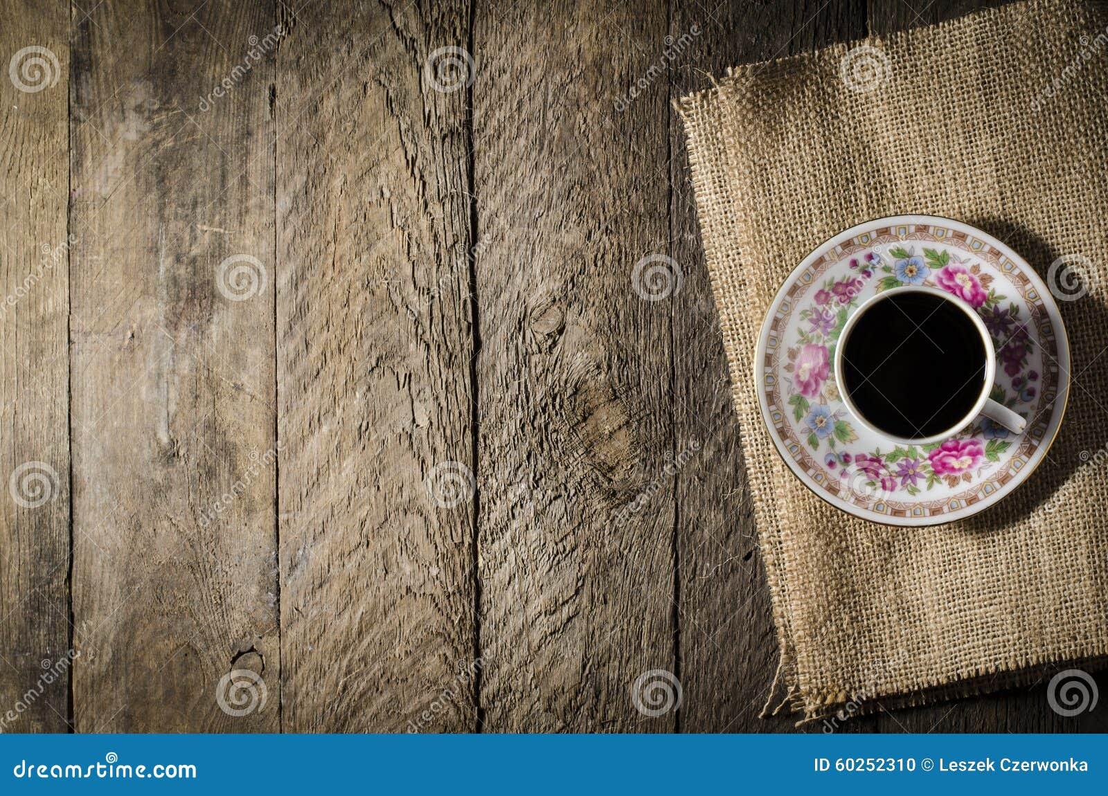 Taza de café de la porcelana en la tabla de madera