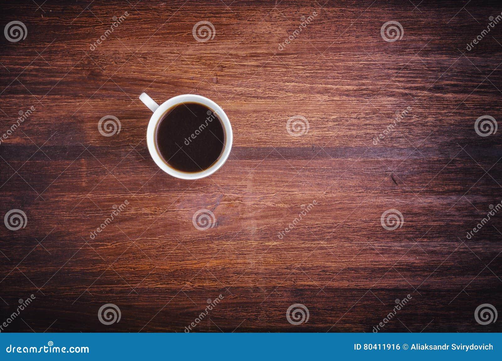 Taza de café en la opinión de sobremesa de madera del marrón oscuro