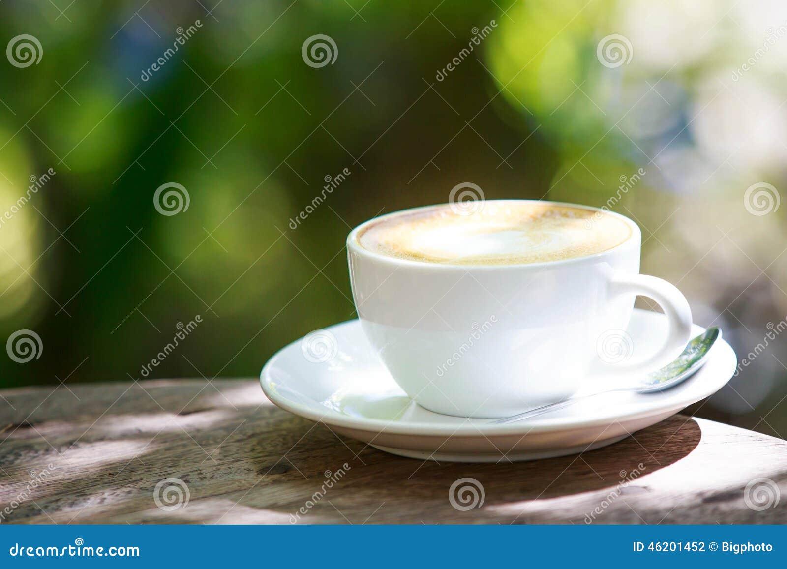 Taza de café en la tabla de madera con el fondo verde del bokeh