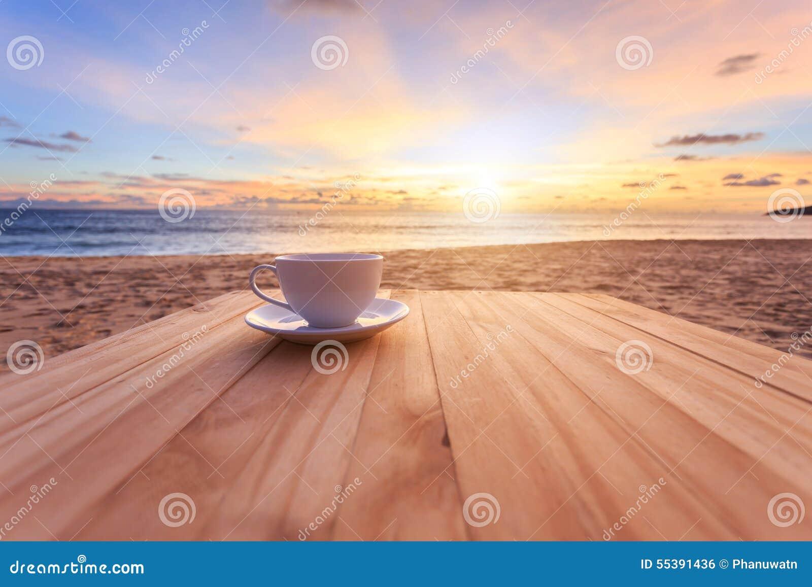 Taza de café en la tabla de madera en la puesta del sol o la playa de la salida del sol