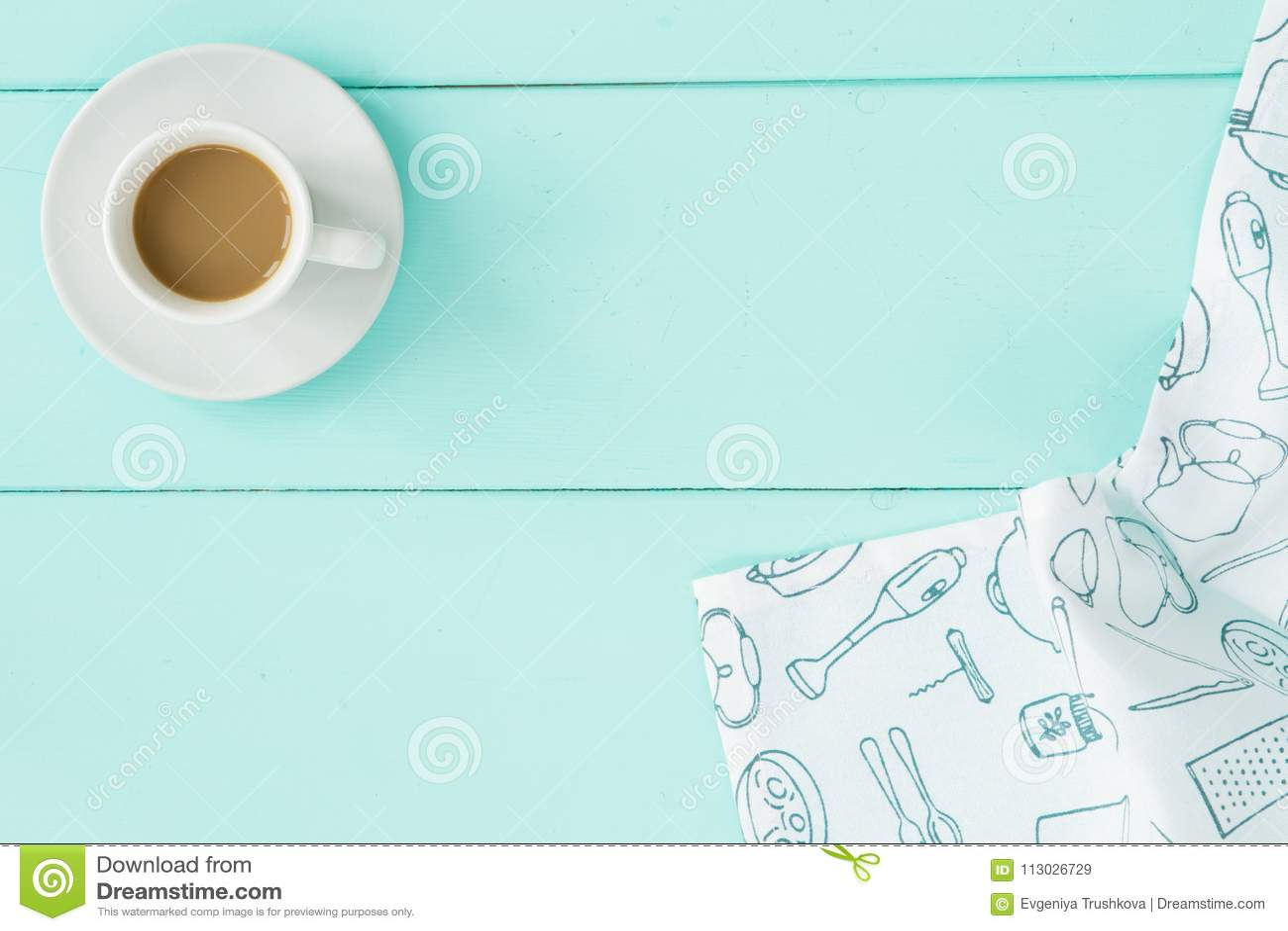 Taza de café en la tabla de la turquesa con la servilleta blanca