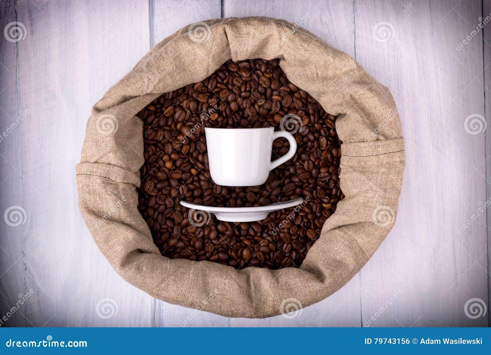 Taza de café en un bolso por completo de los granos de café