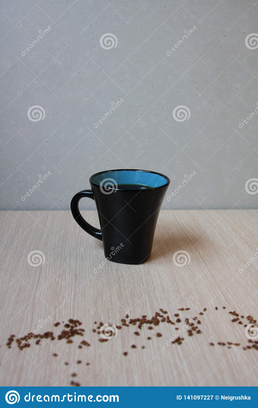Taza de café fresco en fondo ligero con café del polvo del grano